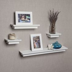 this set of 4 white cornice floating shelves with 2 matching picture frames adds depth to