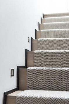 A woven herringbone rug accents a gray wash staircase illuminated by inset light… - Modern Carpet Staircase, Staircase Runner, Staircase Remodel, Design Living Room, Living Spaces, Herringbone Rug, Hallway Designs, House Stairs, Hallway Decorating