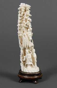 """CHINESE CARVED IVORY TUSK - Vertical carving of man and woman standing at base on a small platform. Overhead are tree forms and mushroom shapes; a small female figure is standing on a ledge. Back carved to represent mountain peaks. Fixed to a wood stand. Apparently unsigned. Condition good overall; appears assembled from 2 pieces or was broken and the (two) pieces glued together. Pre-ban/Mid 20th century to approx 1970. 8.5""""H"""
