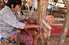Thai silk weaving - A woman uses a wooden loom to weave a silk cloth in a village in Surin, northeast Thailand