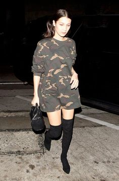 Bella Hadid wears a camouflage Adidas Originals by Kanye West Yeezy Season 1 t-shirt, thigh-high suede boots, and an Alexander Wang duffle bag