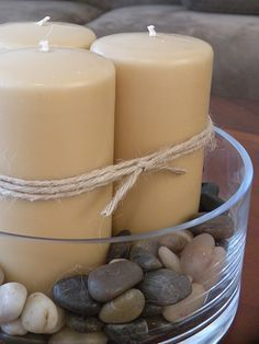 Take cheap candles, wrap them with twine, and place on dollar store rocks in a glass tray for spa bathroom decor