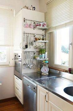 """Il faut prendre un peu de hauteur pour voir la """"bonne idée gain de place"""" dans cette petite cuisine ! En plus d'utiliser le côté de l'armoire pour suspendre des ustensiles et accessoires, on peut également placer des objets ou des appareils encombrants sur le haut de l'armoire ! Le seul inconvénient, c'est salissant..."""