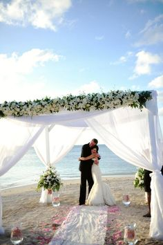 Beautiful ocean backdrop with white Chuppah and aisle covered in delicate flower petals