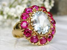 A fabulous vintage aquamarine engagement ring artfully crafted of 14k yellow gold with a combination of rubies and spinel accent stones that is just stunning! The large aquamarine is oval cut measuring approximately 11mm x 9mm or 3.85 carats. The stone is held in place by 12 claw prongs and there is also a circle of 12 combined pinkish red spinels or rubies, presumed to be synthetic measuring approximately 0.10ct each, that adds a lovely framing and color contrast affect to the beautiful…