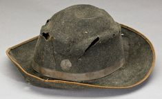 A black hat worn by Buck Ransom, 12th Virginia Cavalry. Ransom was wounded at Brandy Station. The slice in the back of the hat, paralleled by a cut in the lining, is from a saber cut. The spot below the cut is a bloodstain. Ransom's hat has two features in common with other imported hats: a green, striped lining as seen in Munford's hat; and, it is black wool felt.