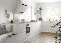 Cuisine blanche contemporaine qui adopte le concept en L aussi fonctionnel qu'esthétique