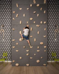 Kids will go ga-ga over this playroom with a climbing wall. The graphic print gray-and-white wallpaper adds an extra layer of cool.