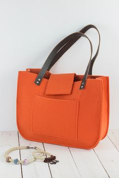Orange felt tote bag,for shopping, genuine leather handles, tote bag, tote felt .  This bag is a simple design but, at the same time very stylish. The size is ideal for carrying magazines, books, notebook or files. Fresh, elegant, casual and much more.  Made of orange felt. Felt is impregnated 4mm (0,16).  Straps are 2 cm (0,79) wide, 61cm (24) long, dark brown Inside and outside large pocket 22cm (8,66  ) / 16,5 (6,50) . The front flap fasten with a magnetic snap or if you I can adjust…