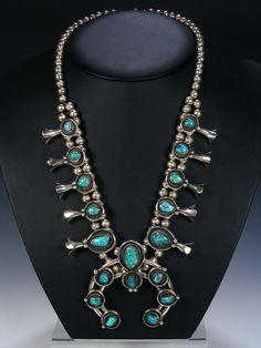 This sterling silver squash blossom necklace features 18 beautiful blue and green turquoise stones surrounded by traditional designs. Strung on two strands of 8