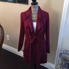"EUC Burgundy long cardi jacket with ruffles! Only worn a few times, this beauty measures 20"" from armpit to armpit and 31-1/2"" from back neckline to hem. Super feminine ruffles are 4 tiered all around the bottom as well as around the neckline. Frog closures in front with a self belt. Really not weather worthy, this is more of an indoor statement. Lightweight material but oh, so pretty!  Cupio Jackets & Coats"
