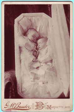 A cabinet card showing twin babies in a open coffin propped up on a shawl-covered armchair.    Photographed by G.W. Bauder of Marinette, Wisconsin.