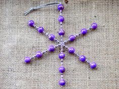 This Christmas tree decoration has been hand-beaded with a selection of purple ceramic, dark silver faceted crystal and seed beads onto a strong metal wire frame. The snowflake is approximately 5.5×4.75″ (140x120mm), and is suspended from a knotted silver cord.  The ceramic and glass crystal beads make this ornament ideal for the higher branches of the tree where children or pets are less likely to knock it off the tree.  Aftercare: the snowflake will need to be wrapped safely for storage…
