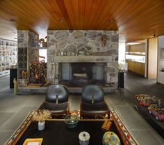 Architect: Alan Goldberg Year: 1977 The living room features a freestanding fireplace as well as bluestone floors, fieldstone walls, and stained natural wood ceilings. The owners' collection of Mexican folk art brings color to the space.
