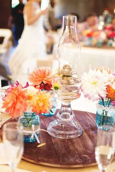 Our simple centerpieces, Dahlia in blue mason jars with lace or ruffle and moms collection of oil lamps sitting on a wine barrel top. Loved it!