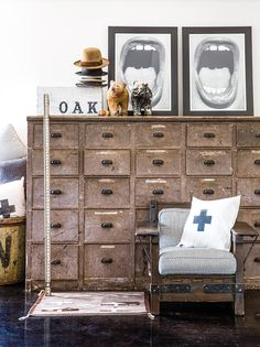 Room with white walls, vintage druggist cabinet, black and white artwork, and a chair with stiped cushions