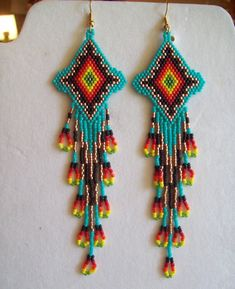 These Beautiful Native American Beaded Earrings are custom made by Elaine out of Turquoise, Black, Copper, Red, Orange, Yellow, and Green. They are 5 1/2 in. long with Gold ear wires on them, can be changed to post or clips. If you like them and want in other color just let me know