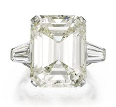 PLATINUM AND DIAMOND RING, J.E. CALDWELL.   Centered by an emerald-cut diamond weighing 20.37 carats, flanked by two tapered baguette diamonds weighing approximately 1.50 carats, size 5½, signed J.E.C. & Co., numbered V470.