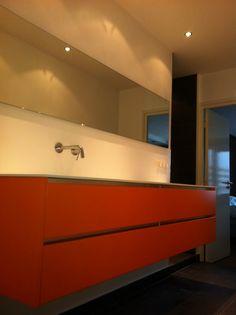 moderne badkamer, met gestukadoorde wanden, oranje badkamer meubel, met alles inbouw kranen. Vloertegels beige en brown collectie mosa. Uitgevoerd door Ennovy keukens en badkamers.