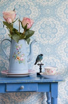 Love the vintage looking wallpaper in blue, the blue table, and painted pitcher with shabby chic roses