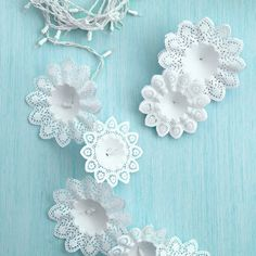 "Snowflake Lights                                    Create an idealized winter wonderland indoors using snowflake-like bouquet holders and a string of holiday lights. To make one of these garlands, slide a store-bought paper bouquet holder over each bulb. Hang the ""snowflakes"" inside a doorway or a window, and then plug in the lights. #christmas"