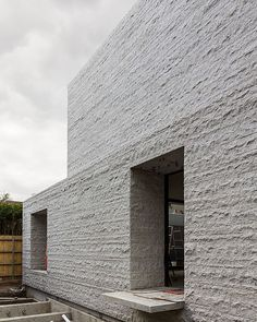 Rear facade in rough granite at the Armadale Residence by B.E Architecture