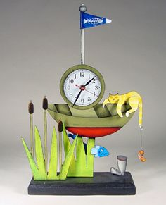 CRAZY CLOCK-the fish is the pendulum,  the whole things is painted metal on a black wood base.