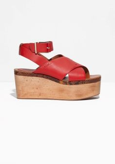 Robust wooden wedges carry those statement-making leather sandals with comfortable ankle straps for added support.