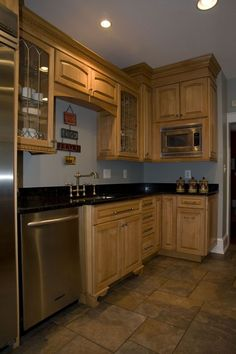 This kitchen includes stainless steel appliances, glass-front cabinetry, and modern fixtures placed throughout the room.