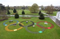 Marking 100 days to go to the London 2012 Olympic Games at the Royal Botanic Gardens, Kew. Standing in the Rings are athletes' families, Torchbearers, Games Maker volunteers, London 2012 Festival participants and schoolchildren - all getting ready to welcome the world in the summer.    The Rings, 15.5 metres each in circumference, are made up of a total of 20,000 plants and are visible from the Heathrow flight path.