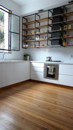 Cocina con piso de madera, mesada de carrara, muebles laqueados y alacena colgante con estantes de madera natural