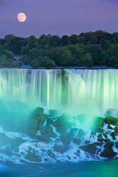 Purple night sky with full moon over emerald green and blue waterfall and large waves