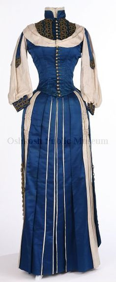 "Dress, ca. 1880  ID:2007-68  ""Bustle dress. A bright blue silk satin dress with rose-colored (now faded to a cream color except where hidden in seams and pleats) silk fabric accents."""