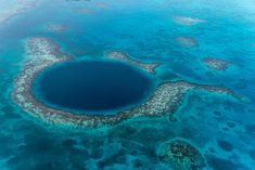 The Great Blue Hole in Belize. The Great Blue Hole is a submarine sinkhole off the coast of Belize. It's one of the top scuba diving sites in the world and the water is 407 feet deep.
