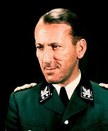 Ernst Kaltenbrunner was an Austrian-born senior official of Nazi Germany during World War II. An Obergruppenführer (general) in the Schutzstaffel (SS), between January 1943 and May 1945 he held the offices of Chief of the Reichssicherheitshauptamt (RSHA, Reich Main Security Office) and President of Interpol. He was the highest-ranking member of the SS to face trial at the first Nuremberg Trials. He was found guilty of war crimes and crimes against humanity and executed.