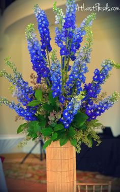 Centerpiece Blue and Gold Wedding Flower Inspirations Delphinium atop gold bamboo accented cylinder Flowers by: At Last Florals