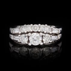 18Kt White Gold Diamond Engagement Ring Set features 3 Round Modified Brilliant Cut Diamonds with a 0.50 carat center.  The 11 accent diamonds on both rings totals 1.02 carats.  Rings are both a size 5.75 and can be re-sized.  The total weight of the 2 ring set is 8.4 grams.