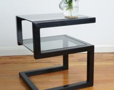 This slender coffee table is perfectly formed to fit into a smaller living room. With a stylish industrial steel frame and clear or tinted glass inset, this table will stand out without dominating your room.  Don't be fooled by the sleek dimensions - the steel frame is handmade from 40mm industrial steel ensuring a robust construction and can be supplied either powder coated in black satin finish or clear lacquered raw steel for a more industrial look.  If you fancy another colour or a… Contemporary Glass Coffee Tables, Steel Furniture, Furniture Chairs, Furniture Design, Iron Furniture, Garden Furniture, Kids Furniture, Furniture Plans, Bedroom Furniture