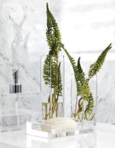 The clear bathroom accessories, Carrara marble and the occasional splash of green found in this bathroom feel like they could be found in a spa. {Photography by Virginia Macdonald}View more here: http://www.styleathome.com/homes/interiors/interiors-hotel-style-glam/a/46447/13