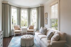 Elegant sitting room features a bay window dressed in gray green drapes filled with beige bergere chairs and a round marble top table atop wood floors.