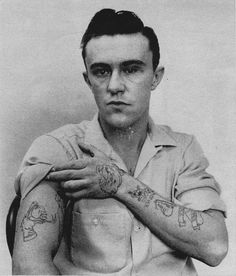 """Richard """"Dick"""" Hickock displays his tattoos for police photographs."""