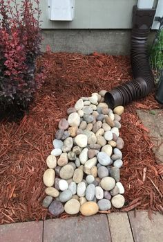 River rock bed added below downspout so that mulch is not washed onto the sidewalk by the rain.
