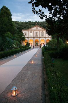 A tan runner flanked with lanterns leads to the grand entrance.