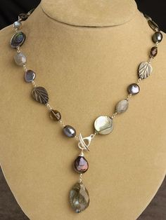 JK:  I really like these colors.  The focal looks like labradorite, and the beads are mostly pearl and abalone.  The smaller brown ones are either smokey quartz or glass, and the light grey may be moonstone.