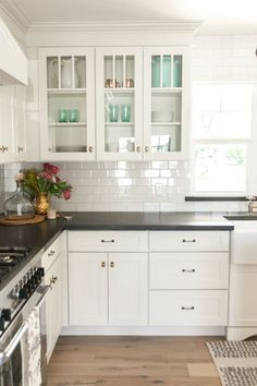 White kitchen cabinets, black countertops and white subway tile with white grout. Love the look!