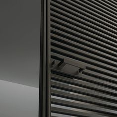 slim sliding Even door, characterized by the thin jamb. Brown aluminium structure and grey transparent glass.