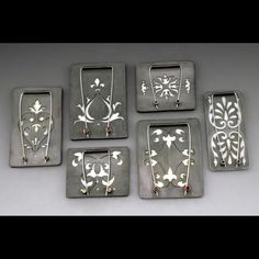 Photo-enameled on steel, hand fabricated of sterling. The backs are hand pierced with tube set rubies, emeralds, and peridots set in the clasps.