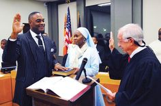 With his wife Abisayo by his side, Marcus Muhammad is officially sworn in as Mayor of Benton Harbor, Michigan by former Chief Justice of Berrien County Judge Alfred Butzbaugh Dec. 23. Photo: Haroon Rajaee