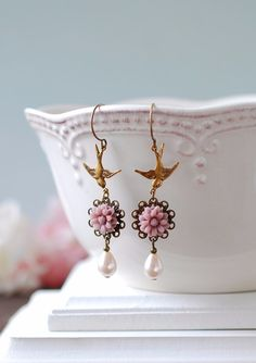 【Vintage Style Jewelry Collection】Mauve Flower Soft Pink Glass Pearls Brass Bird Pierceこちらはビンテージ風 ジュエリー コレクションのピアスになります。全ての金具をヴィンテージ風加工し印象的な鳥のチャームに加え鮮やかな薄紫のレジンフラワーとスワロフスキー社のクリスタルパールをあしらったピアスです。These unique long dangle earrings are created from beautifully detailed antique brass birds, lovely mauve daisy resin flowers, brass lace filigrees and light pink teardrop glass pearls. サイズ▷  ピアス部分も含めた全体の長さ:約65mmスワロフスキー パール:9mm x 7mm素材▷  【素材】金属フック(金古美カラー)、金属金具(金古美カラー)レジンフラワー、スワロフスキー社のクリスタル…