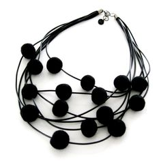 Halsband av gummi och ullbollar. Necklace, rubber and wool beads